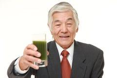 Ανώτερος ιαπωνικός επιχειρηματίας με τον πράσινο φυτικό χυμό Στοκ Εικόνες