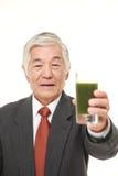 Ανώτερος ιαπωνικός επιχειρηματίας με τον πράσινο φυτικό χυμό Στοκ Φωτογραφίες