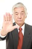 Ανώτερος ιαπωνικός επιχειρηματίας που κάνει τη χειρονομία στάσεων Στοκ Εικόνα