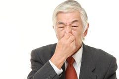 Ανώτερος ιαπωνικός επιχειρηματίας που κρατά τη μύτη του λόγω μιας κακής μυρωδιάς Στοκ φωτογραφίες με δικαίωμα ελεύθερης χρήσης