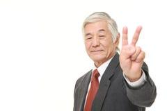 Ανώτερος ιαπωνικός επιχειρηματίας που παρουσιάζει σημάδι νίκης Στοκ φωτογραφία με δικαίωμα ελεύθερης χρήσης