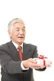 Ανώτερος ιαπωνικός επιχειρηματίας που προσφέρει ένα δώρο Στοκ Εικόνα