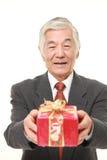 Ανώτερος ιαπωνικός επιχειρηματίας που προσφέρει ένα δώρο Στοκ εικόνα με δικαίωμα ελεύθερης χρήσης
