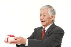 Ανώτερος ιαπωνικός επιχειρηματίας που προσφέρει ένα δώρο Στοκ Εικόνες