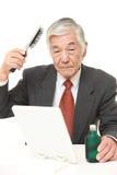 Ανώτερος ιαπωνικός επιχειρηματίας που χρησιμοποιεί τον αποκαταστάτη τρίχας Στοκ Εικόνα