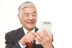 Ανώτερος ιαπωνικός επιχειρηματίας που χρησιμοποιεί τον υπολογιστή ταμπλετών Στοκ εικόνες με δικαίωμα ελεύθερης χρήσης