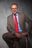 Ανώτερος διευθυντής που φορά την τοποθέτηση γυαλιών που κάθεται Στοκ Εικόνες