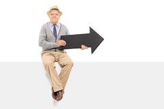 Ανώτερος κύριος που κρατά ένα βέλος καθισμένο στην επιτροπή Στοκ Φωτογραφίες