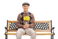 Ανώτερος κύριος που κρατά μια δέσμη των λουλουδιών Στοκ Εικόνες