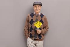 Ανώτερος κύριος που κρατά μια δέσμη των λουλουδιών Στοκ φωτογραφία με δικαίωμα ελεύθερης χρήσης