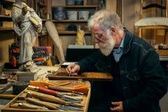 Ανώτερος ξύλινος επαγγελματίας γλυπτικής κατά τη διάρκεια της εργασίας Στοκ φωτογραφίες με δικαίωμα ελεύθερης χρήσης