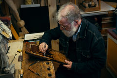 Ανώτερος ξύλινος επαγγελματίας γλυπτικής κατά τη διάρκεια της εργασίας Στοκ Φωτογραφία