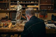 Ανώτερος ξύλινος επαγγελματίας γλυπτικής κατά τη διάρκεια της εργασίας Στοκ Εικόνες