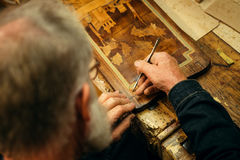 Ανώτερος ξύλινος επαγγελματίας γλυπτικής κατά τη διάρκεια της εργασίας Στοκ φωτογραφία με δικαίωμα ελεύθερης χρήσης