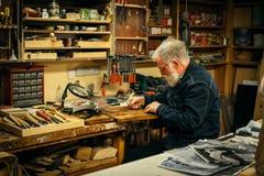 Ανώτερος ξύλινος επαγγελματίας γλυπτικής κατά τη διάρκεια της εργασίας Στοκ εικόνα με δικαίωμα ελεύθερης χρήσης