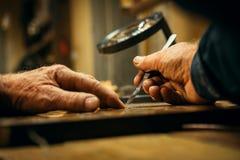 Ανώτερος ξύλινος επαγγελματίας γλυπτικής κατά τη διάρκεια της εργασίας Στοκ Εικόνα