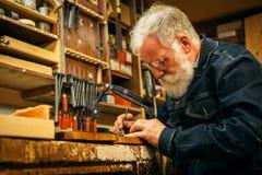 Ανώτερος ξύλινος επαγγελματίας γλυπτικής κατά τη διάρκεια της εργασίας Στοκ Φωτογραφίες