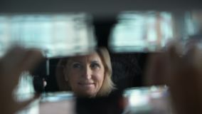Ανώτερος οδηγός που γυρίζει τον οπισθοσκόπο καθρέφτη, αντανάκλαση του χαμογελώντας θηλυκού επιβάτη απόθεμα βίντεο