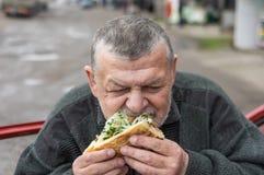 Ανώτερος οδηγός που τρώει το lyulya kebab στο lavash κοντά στο αυτοκίνητό του στοκ εικόνες με δικαίωμα ελεύθερης χρήσης