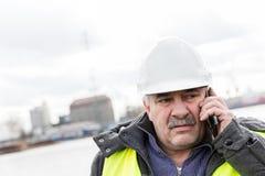 Ανώτερος οικοδόμος μηχανικών στο τηλέφωνο στο εργοτάξιο οικοδομής Στοκ εικόνες με δικαίωμα ελεύθερης χρήσης