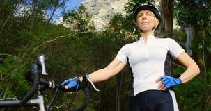 Ανώτερος ποδηλάτης που στέκεται με το ποδήλατο στην επαρχία 4k απόθεμα βίντεο