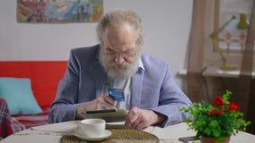 Ανώτερος συνταξιούχος που κάνει την αγορά πιστωτικών καρτών στον καφέ φιλμ μικρού μήκους