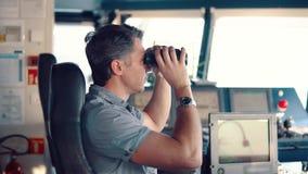 Ανώτερος υπάλληλος κατά τη διάρκεια του πλοήγησης ρολογιού που κοιτάζει μέσω των διοπτρών απόθεμα βίντεο