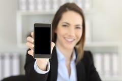 Ανώτερος υπάλληλος που παρουσιάζει κενό έξυπνο τηλέφωνο στο γραφείο Στοκ φωτογραφίες με δικαίωμα ελεύθερης χρήσης