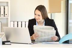 Ανώτερος υπάλληλος που συγκρίνει τις ειδήσεις on-line με μια εφημερίδα Στοκ εικόνα με δικαίωμα ελεύθερης χρήσης