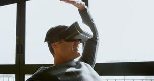 Ανώτερος υπάλληλος που χρησιμοποιεί την κάσκα εικονικής πραγματικότητας στο γραφείο 4k απόθεμα βίντεο