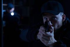 Ανώτερος υπάλληλος που δείχνει το πυροβόλο όπλο στον εγκληματία στοκ εικόνες με δικαίωμα ελεύθερης χρήσης