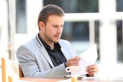 Ανώτερος υπάλληλος που διαβάζει μια επιστολή σε μια καφετερία Στοκ Φωτογραφία
