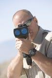 Ανώτερος υπάλληλος που κοιτάζει μέσω του πυροβόλου όπλου ραντάρ Στοκ Εικόνες