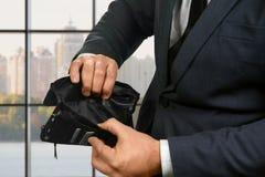 Ανώτερος υπάλληλος που κρατά ένα κενό πορτοφόλι Στοκ Εικόνες
