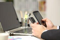 Ανώτερος υπάλληλος που συγχρονίζει το έξυπνα ρολόι και το τηλέφωνο Στοκ Εικόνες