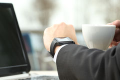 Ανώτερος υπάλληλος που συμβουλεύεται ένα έξυπνο ρολόι σε έναν φραγμό Στοκ Φωτογραφίες