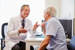 Ανώτερος υπομονετικός διοργανώνοντας τις διαβουλεύσεις με το γιατρό στην αρχή στοκ φωτογραφία