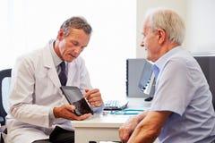 Ανώτερος υπομονετικός διοργανώνοντας τις διαβουλεύσεις με το γιατρό στην αρχή στοκ φωτογραφία με δικαίωμα ελεύθερης χρήσης