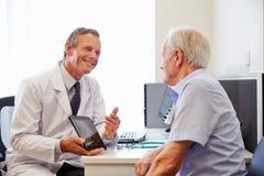 Ανώτερος υπομονετικός διοργανώνοντας τις διαβουλεύσεις με το γιατρό στην αρχή στοκ εικόνα με δικαίωμα ελεύθερης χρήσης