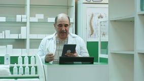 Ανώτερος φαρμακοποιός που έχει την τηλεοπτική συνομιλία με τον πελάτη που χρησιμοποιεί το PC ταμπλετών στο φαρμακείο απόθεμα βίντεο