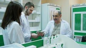 Ανώτερος φαρμακοποιός που δίνει το μισθό σε δολάριο στους νέους συναδέλφους του στο φαρμακείο στοκ εικόνα