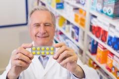 Ανώτερος φαρμακοποιός που κρατά ψηλά τα πακέτα φουσκαλών στοκ εικόνα