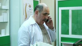 Ανώτερος φαρμακοποιός που μιλά στο κινητό τηλέφωνο ελέγχοντας τη συνταγή στο φαρμακείο απόθεμα βίντεο
