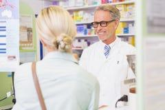 Ανώτερος φαρμακοποιός που μιλά με τον πελάτη στοκ εικόνα με δικαίωμα ελεύθερης χρήσης