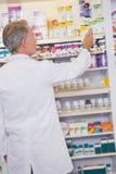 Ανώτερος φαρμακοποιός που παίρνει το κιβώτιο από το ράφι στοκ εικόνα με δικαίωμα ελεύθερης χρήσης