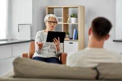 Ανώτερος ψυχολόγος με το PC ταμπλετών και ασθενής στοκ φωτογραφία