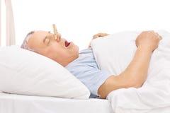 Ανώτερος ύπνος με ένα clothespin στη μύτη του στοκ φωτογραφίες με δικαίωμα ελεύθερης χρήσης