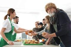 Ανώτερο άτομο με άλλους φτωχούς ανθρώπους που λαμβάνουν τα τρόφιμα από τους εθελοντές στοκ εικόνα με δικαίωμα ελεύθερης χρήσης