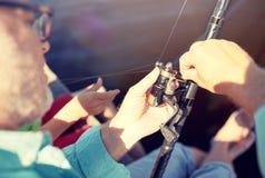 Ανώτερο άτομο με την αλιεία της ράβδου ή την περιστροφή στον ποταμό στοκ φωτογραφίες