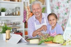 Ανώτερο άτομο με την εγγονή που προετοιμάζει το γεύμα Στοκ εικόνα με δικαίωμα ελεύθερης χρήσης